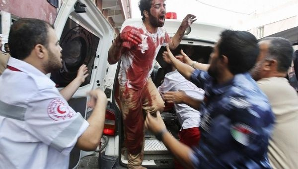 A Palestinian man cries in clothes stained with the blood of his father, who medics said was killed by Israeli shelling