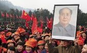 A man holds up a portrait of the late Chinese revolutionary leader, Chairman Mao Zedong.