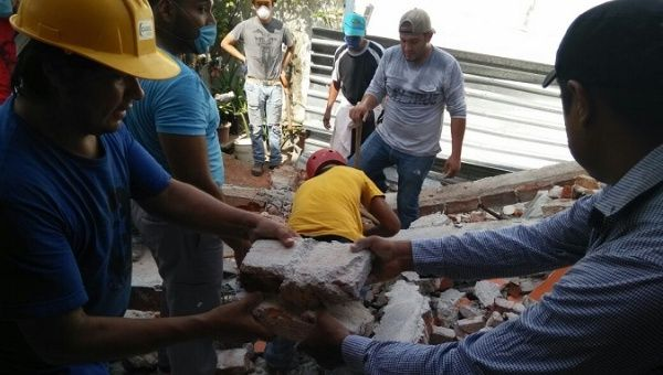 Volunteers remove rubble from a collapsed buidling in Cuernavaca, Morelos.