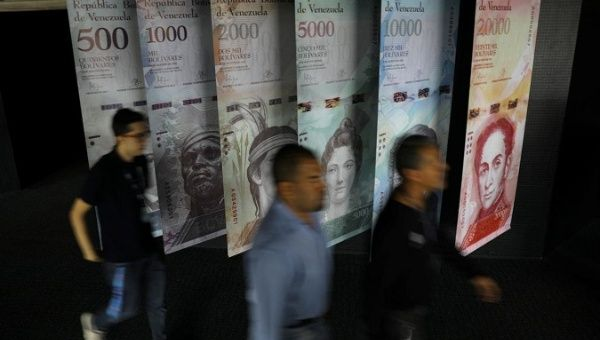 People walk by banners of Venezuelan bolivar notes displayed at the Venezuelan Central Bank building in Caracas, Venezuela.