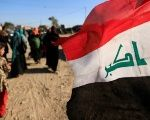 A child walks past the Flag of Iraq.