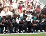 NFL players from the Baltimore Ravens knelt during the national anthem Sunday after Trump called on fans to boycott teams that do not discipline players.