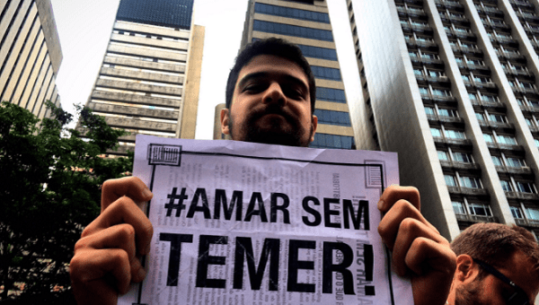 "A protester holds a sign with the message ""Love without Temer."""