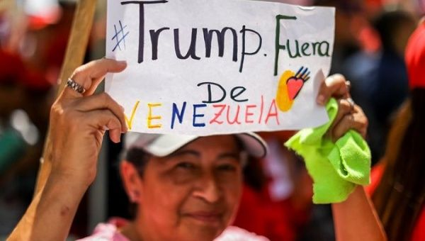 "A protester hold a sign reading ""Stay out of Venezuela Trump"""
