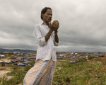 A refugee prays on a hill overlooking Kutupalong camp after another Rohingya burial.