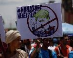 A supporter of Venezuela's Bolivarian Revolution holds a placard depicting Trump during a rally against imperialism in Venezuela, Sept. 19, 2017.