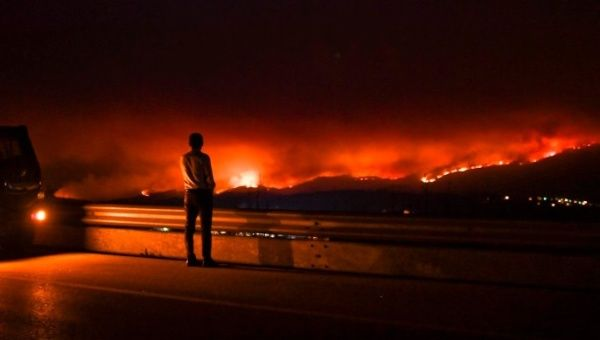 A man stands on the roadside watching a wildfire at Anciao, Leiria, central Portugal.
