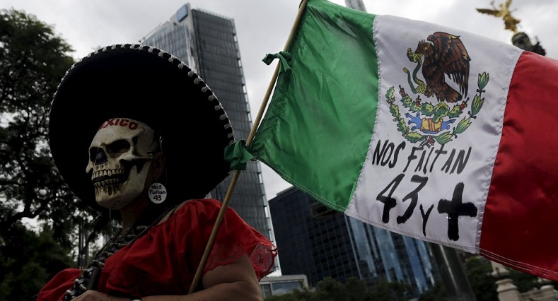 A woman dressed as a skeleton takes part in a march in Mexico City, with a 43 written on the Mexican flag.