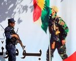 An Iraqi policeman stands next to a banner supporting the referendum for independence of Kurdistan in Erbil, Iraq.