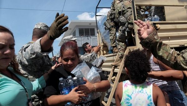 A woman carries bottles of water and food during a distribution of relief items, after the area was hit by Hurricane Maria in San Juan.