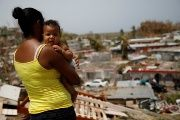 A woman carrying her son looks at the damage in the neighborhood after the area was hit by Hurricane Maria, in Canovanas, Puerto Rico.