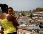 Ysamar Figueroa carrying her son Saniel, looks at the damage in the neighbourhood after the area was hit by Hurricane Maria, Sept. 26, 2017.