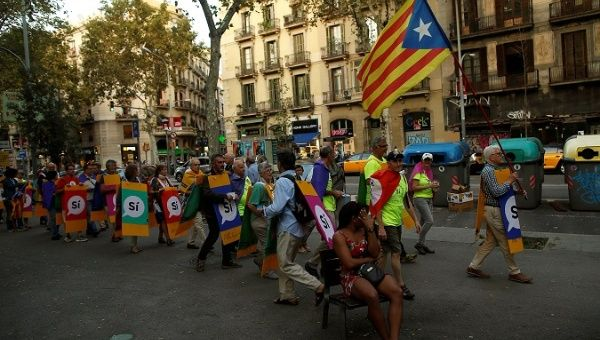 "Members of Catalan National Assembly (ANC) carry signs that read, ""Yes"", and an Estelada (Catalan separatist flag) during a protest."