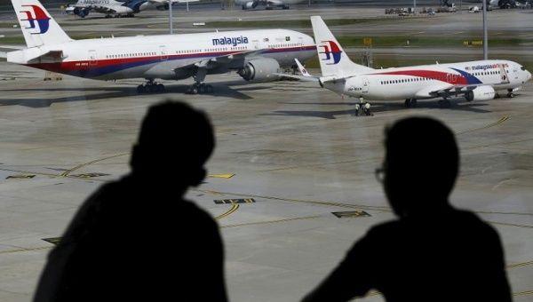 Men watch Malaysia Airlines aircraft at Kuala Lumpur International Airport in Sepang, Malaysia.
