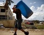 A man carries a container filled with water after the area was hit by Hurricane Maria in Toa Baja, Puerto Rico