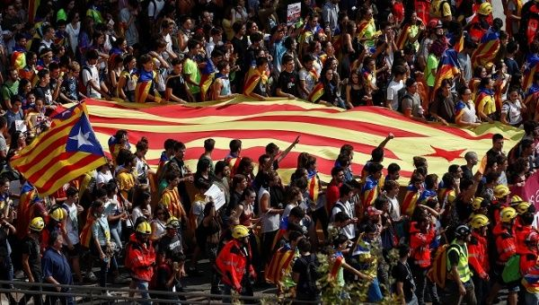 Demonstrators in Barcelona carry a giant Catalan flag.