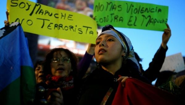 "A Mapuche activist attends a protest in Santiago. The signs read:"" I am Mapuche, not terrorist"" and ""No more violence against Mapuche""."