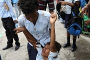 A girl holds a friend affected by tear gas after Haitian National Police officers fired it to disperse a demonstration against the government in Port-au-Prince.