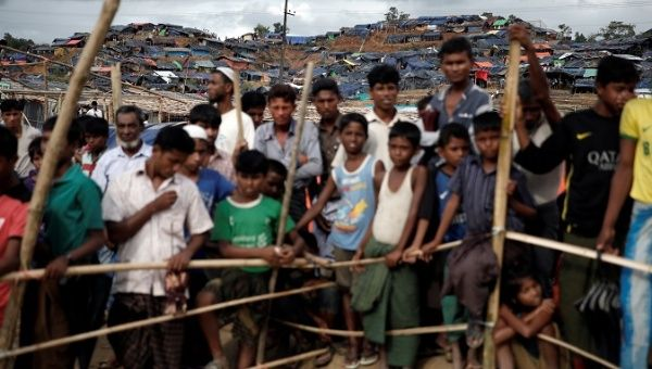 Rohingya refugees queue for aid at a camp in Cox
