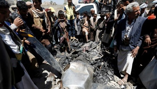 People gather around the engine of a drone aircraft which the Houthi rebels said they have downed in Sanaa, Yemen Oct. 1, 2017.