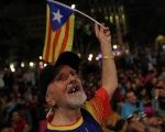 A man waves an Estelada as people gather at Plaza Catalunya after voting ended for the banned independence referendum in Barcelona, Spain, Oct. 1, 2017.