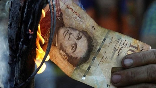 A man burns a 100-bolivar bill during a protest in El Pinal, Venezuela.