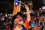 A man waves an Estelada (Catalan separatist flag) as people gather at Plaza Catalunya after voting ended for the independence referendum on Sunday.