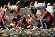 People scramble for shelter at the Route 91 Harvest country music festival after gunfire was heard in Las Vegas, Nevada.