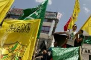 Palestinian demonstrators hold Fatah and Hamas party flags as they demonstrate. (FILE)