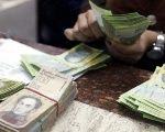 A cashier counts bolivars at money exchange in Caracas.