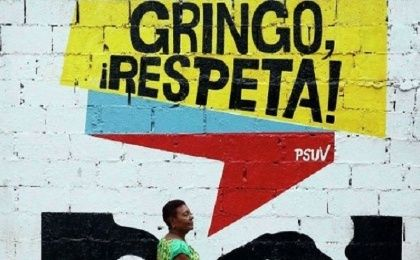"A woman walks by a sign in Venezuela that reads, ""Gringo Respect!"""