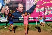 Children play in front of a campaign poster of Daniel Ortega and Rosario Murillo in Managua, Nicaragua.