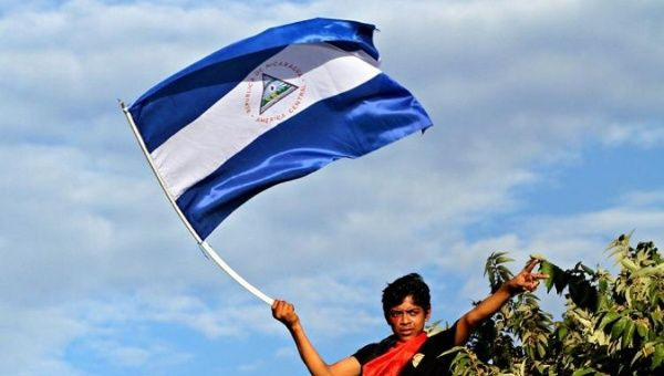 A supporter of the Sandinista National Liberation Front waves the Nicaraguan flag.