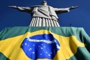 Brazil's flag beneath Christ the Redeemer statue in the city of Rio de Janeiro.