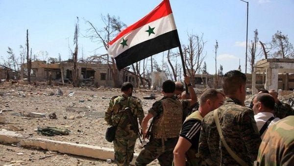 シリア陸軍は、シリアの国旗を掲げ軍事施設を過ぎて歩いている。