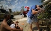 A resident washes her hair with water from a pipe on the side of a road days after Hurricane Maria hit Puerto Rico.