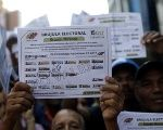 A supporter of Wilmer Nolasco, candidate for Miranda State government, holds a replica of an election ballot in Caracas, Venezuela, October 6, 2017.