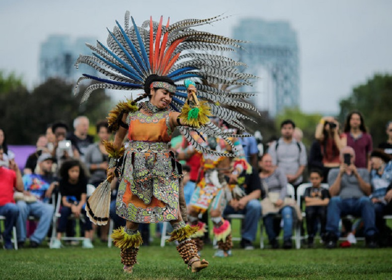 "A reveller performs during a ""pow-wow"" celebrating the Indigenous Peoples"