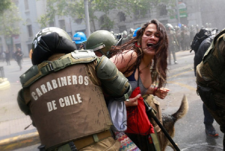 A demonstrator is detained by riot police during a rally against Columbus Day in downtown Santiago.