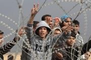Palestinian youths gesture during a demonstration next to the security fence standing on the Gaza border.
