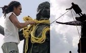 Venezuelan demonstrators use ropes to take down a Christopher Columbus statue in Caracas, Venezuela, October 12, 2004.