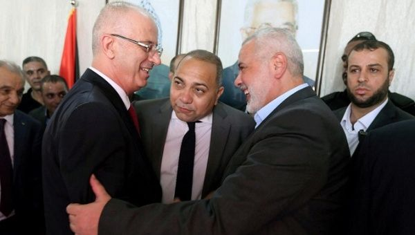 Palestinian Prime Minister Rami Hamdallah (L)  of Fatah shakes hands with Hamas Chief Ismail Haniyeh in Gaza City October 2, 2017.