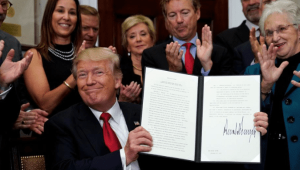 President Trump smiles after signing the Executive Order.