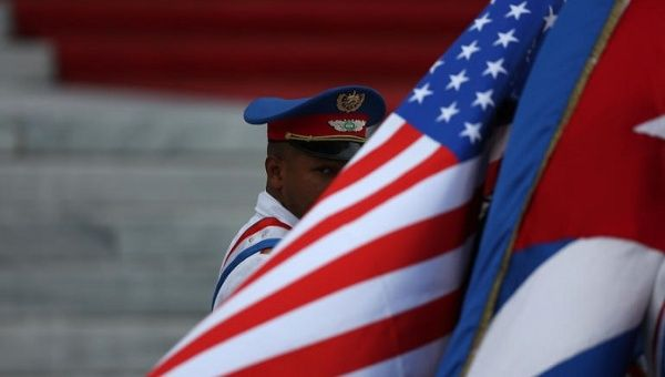 An honor guard peers out from behind U.S. and Cuban flags at the bottom of the steps of the Revolution Palace in Cuba.
