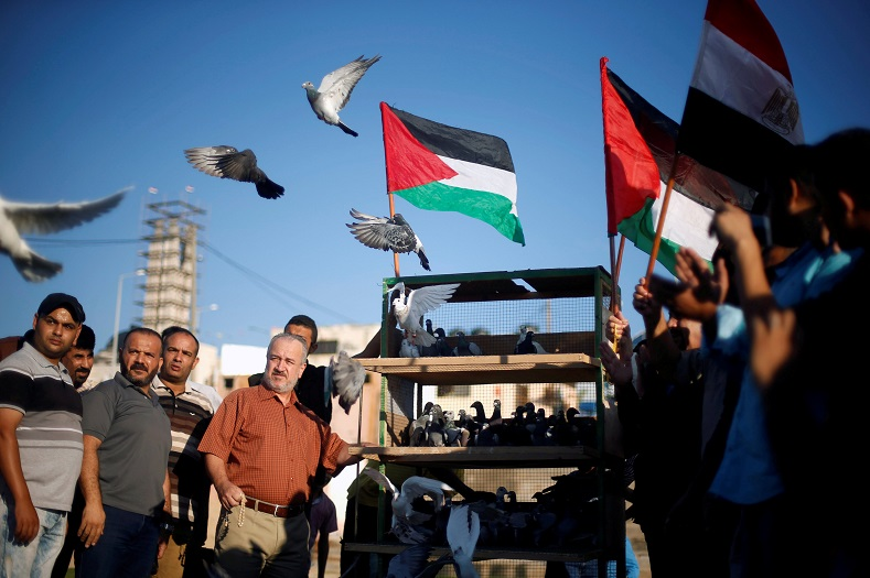 People release pigeons during an event to show support for a unity deal between rival Palestinian factions Hamas and Fatah, in Gaza City.