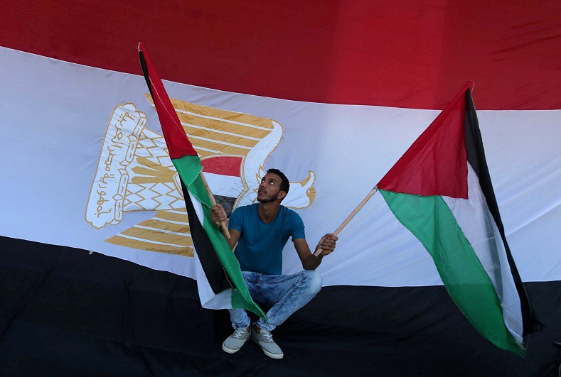 A man holds Palestinian flags as an Egyptian flag is seen in the background during celebrations after Hamas said it reached a deal with Fatah.