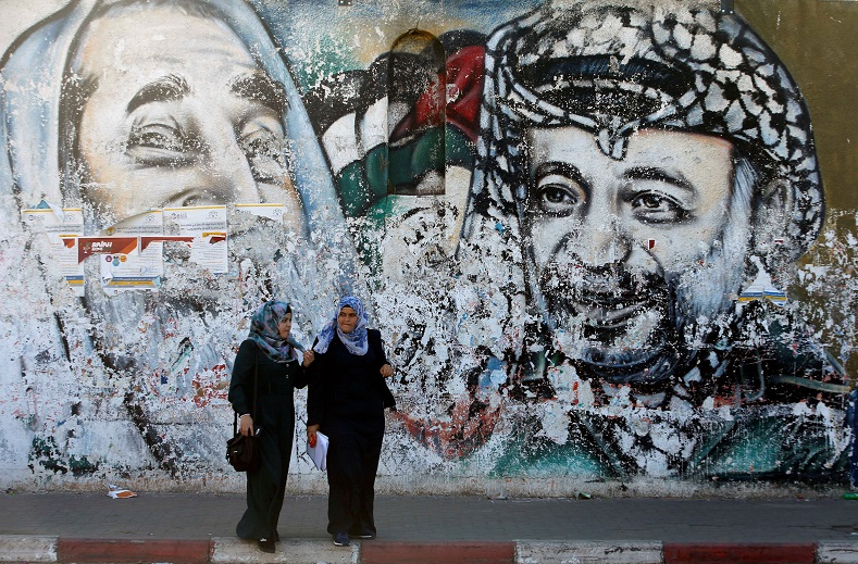 Palestinian students stand in front of a mural depicting late Hamas leader Ahmed Yassin and late Palestinian leader Yasser Arafat, in Gaza City.