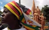 A Zimbabwean woman stands in front of a statue depicting national heroes.