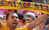 "A man holds up a scarf that reads ""Catalunya."""