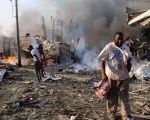Civilians walk at the scene of an explosion in KM4 street in the Hodan district of Mogadishu.